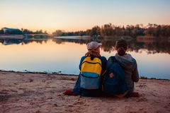 Pares de turistas con las mochilas que se relajan por la orilla del r?o del oto?o Agua potable de las mujeres juguetonas y resto  fotos de archivo libres de regalías