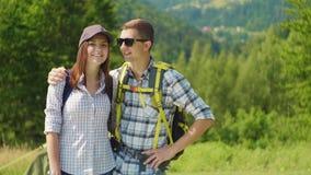 Pares de turistas felices jovenes con las mochilas Miran la cámara y sonríen almacen de video