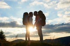 Pares de turistas no amor com as trouxas que enfrentam-se no por do sol nas montanhas foto de stock