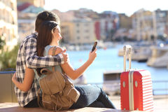 Pares de turistas que procuram em um telefone esperto imagem de stock royalty free