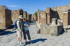 Pares de turistas que visitam as ruínas em Pompeii Fotografia de Stock Royalty Free