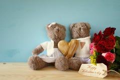 Pares de ursos de peluche bonitos que guardam um coração Imagem de Stock
