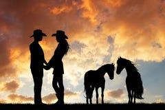 Pares de vaqueros con el caballo en la puesta del sol ilustración del vector