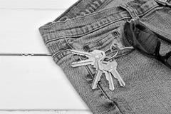 Pares de vaqueros viejos, sistema de llaves de la casa, y gafas de sol imagen de archivo