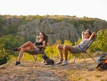 Pares de viagem em um fundo natural Turistas que sentam-se em cadeiras em um parque nacional Conceito de relaxamento Copie o espa foto de stock royalty free