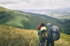 Pares de viajantes com as trouxas que olham nos montes Imagens de Stock Royalty Free