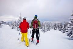 Pares de viajantes em sapatos de neve Foto de Stock
