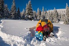 Pares de viajantes que sentam-se, vestindo nos sapatos de neve perto de uma barraca Imagem de Stock