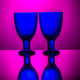 Pares de vidrios azules en un fondo rosado Fotografía de archivo libre de regalías