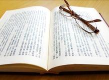 Pares de vidrios en el libro chino Imagen de archivo libre de regalías