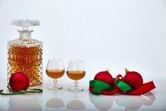 Pares de vidrios y de botella del licor con los ornamentos de la Navidad, los fondos blancos y las reflexiones fotografía de archivo