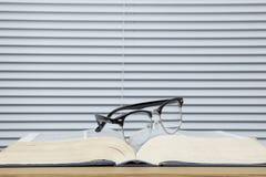 Pares de vidros do olho em um livro de texto aberto gasto Fotos de Stock Royalty Free
