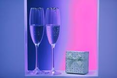 Pares de vidros de néon do champanhe nos feriados interiores fotos de stock