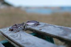 Pares de vidros que encontram-se em um banco ao lado do mar Imagem de Stock