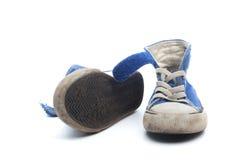 Pares de zapatillas de deporte azules sucias, usadas de los niños Fotografía de archivo libre de regalías