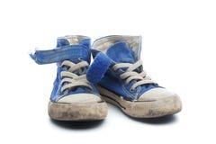 Pares de zapatillas de deporte azules sucias, usadas de los niños Foto de archivo