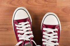 Pares de zapatillas de deporte rojas en piso de madera Fotografía de archivo libre de regalías