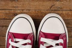 Pares de zapatillas de deporte rojas en viejo fondo de madera retro Foto de archivo
