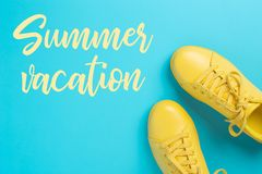 Pares de zapatos amarillos en fondo azul con vacaciones de verano de la inscripción Foto de archivo
