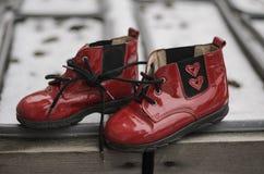 Pares de zapatos de bebé rojos con dos corazones para que el recién nacido lleve Un regalo para el día del ` s de la tarjeta del  Fotos de archivo