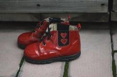 Pares de zapatos de bebé rojos con dos corazones para que el recién nacido lleve Un regalo para el día del ` s de la tarjeta del  Imagen de archivo libre de regalías