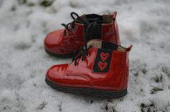 Pares de zapatos de bebé rojos con dos corazones para que el recién nacido lleve Un regalo para el día del ` s de la tarjeta del  Fotos de archivo libres de regalías