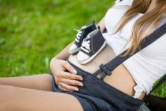 Pares de zapatos de bebé en el abdomen de la mujer embarazada que miente en hierba Foto de archivo