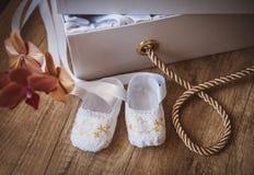 Pares de zapatos de bebé que se sientan en la manta del bebé con el espacio de la copia Fotografía de archivo