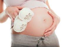 Pares de zapatos de la explotación agrícola de la mujer embarazada para el bebé Fotografía de archivo libre de regalías