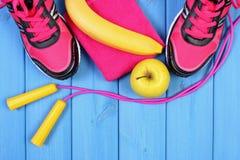 Pares de zapatos del deporte, de frutas frescas y de accesorios para la aptitud en tableros azules, espacio de la copia para el t Foto de archivo libre de regalías