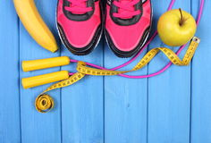 Pares de zapatos del deporte, de frutas frescas y de accesorios para la aptitud en tableros azules, espacio de la copia para el t Imagen de archivo