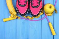 Pares de zapatos del deporte, de frutas frescas y de accesorios para la aptitud en tableros azules, espacio de la copia para el t Fotografía de archivo
