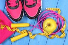 Pares de zapatos del deporte, de manzana fresca y de accesorios para la aptitud en tableros azules Fotografía de archivo