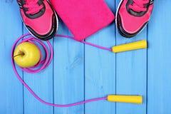 Pares de zapatos del deporte, de manzana fresca y de accesorios para la aptitud en tableros azules, espacio de la copia para el t Fotos de archivo libres de regalías