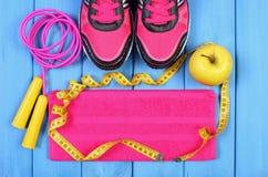 Pares de zapatos del deporte, de manzana fresca y de accesorios para la aptitud en tableros azules, espacio de la copia para el t Imagen de archivo libre de regalías