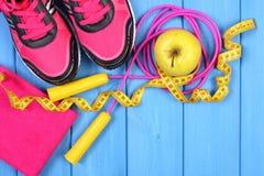 Pares de zapatos del deporte, de manzana fresca y de accesorios para la aptitud en tableros azules, espacio de la copia para el t Fotos de archivo