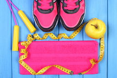 Pares de zapatos del deporte, de manzana fresca y de accesorios para la aptitud en tableros azules, espacio de la copia para el t Fotografía de archivo