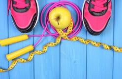 Pares de zapatos del deporte, de manzana fresca y de accesorios para la aptitud en tableros azules, espacio de la copia para el t Imágenes de archivo libres de regalías