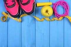 Pares de zapatos del deporte, de manzana fresca y de accesorios para la aptitud en tableros azules, espacio de la copia para el t Foto de archivo libre de regalías