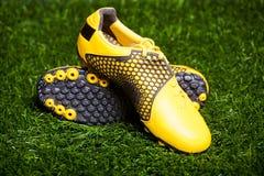 Pares de zapatos del fútbol en campo de hierba Fotos de archivo libres de regalías