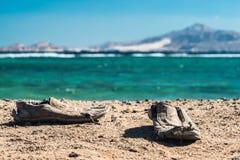 Pares de zapatos lamentables viejos en la playa arenosa Zapatos lamentables viejos en la arena Foto de archivo libre de regalías