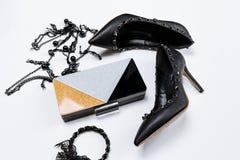 Pares de zapatos negros adornados con acentos del metal, joyer?a con el cord?n y las gotas negros y un embrague tricolor con las  imagen de archivo libre de regalías
