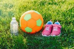 Pares de zapatos rosados de las zapatillas de deporte de la muchacha, balón de fútbol de la tela del niño y botella suaves de agu Imagen de archivo