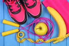 Pares de zapatos rosados del deporte, de frutas frescas y de accesorios para la aptitud en tableros azules Fotografía de archivo