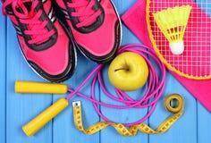 Pares de zapatos rosados del deporte, de manzana fresca y de accesorios para el deporte en tableros azules Fotos de archivo