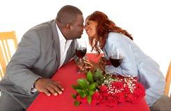 Pares del afroamericano alrededor a besarse en cena romántica Imagen de archivo