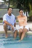 Pares del afroamericano por la piscina Foto de archivo libre de regalías