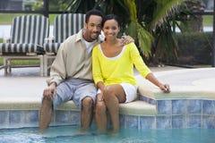 Pares del afroamericano que se sientan por una piscina Fotos de archivo libres de regalías