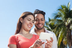 Pares del amor que miran las fotos en el teléfono celular Imágenes de archivo libres de regalías