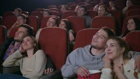 Pares del amor que miran película en el cine Gente joven que come las palomitas almacen de video